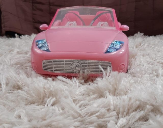 A Pink Barbie Convertible Car On A White Carpet