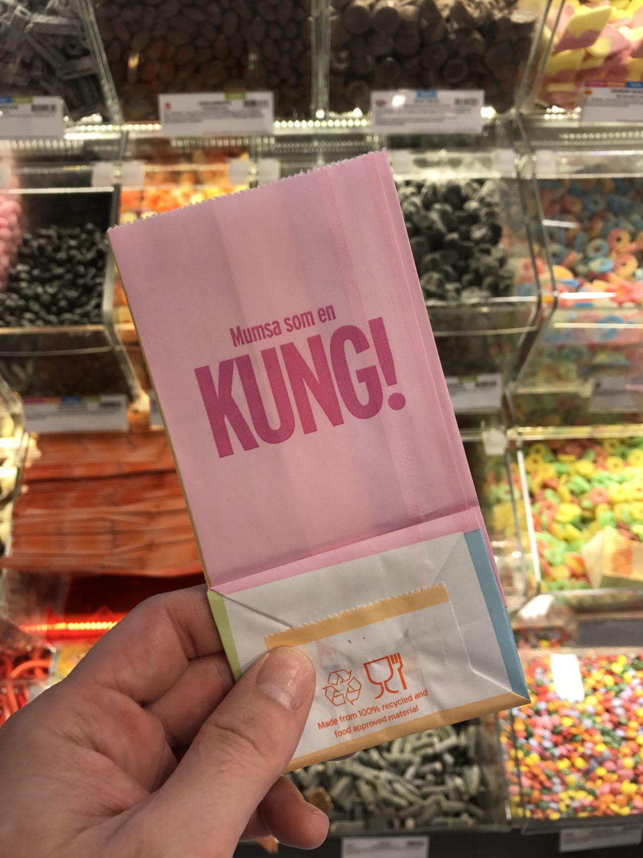 Pink Paper Candy Bag With Candy In The Background