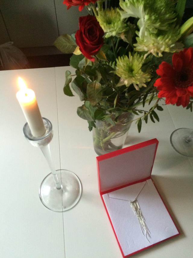 Silver Necklace In A Red Box On White Table With Flowers And Lighted Candle In Candlestick