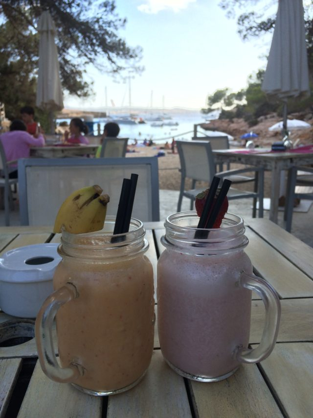 Banana Smoothie And Strawberry Smoothie With Straw On A Wooden Table With Beach As Background