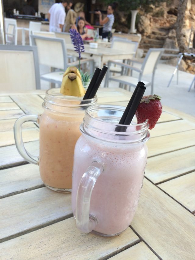 Yellow And Pink Smoothies With Banana Fruit On Glass Edge With People And Flower Background