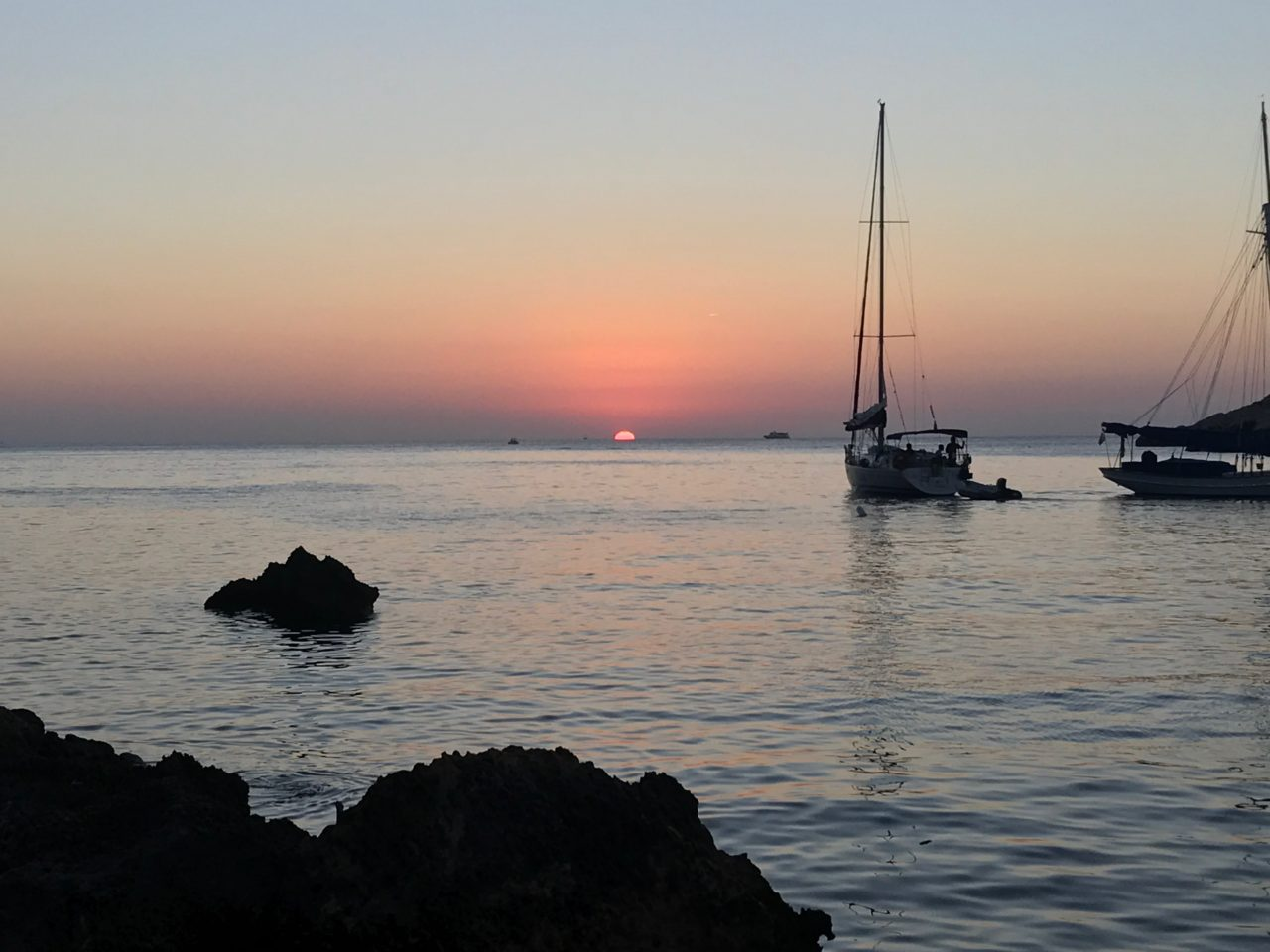 Sunset On A Spanish Beach With Rocks And Boats