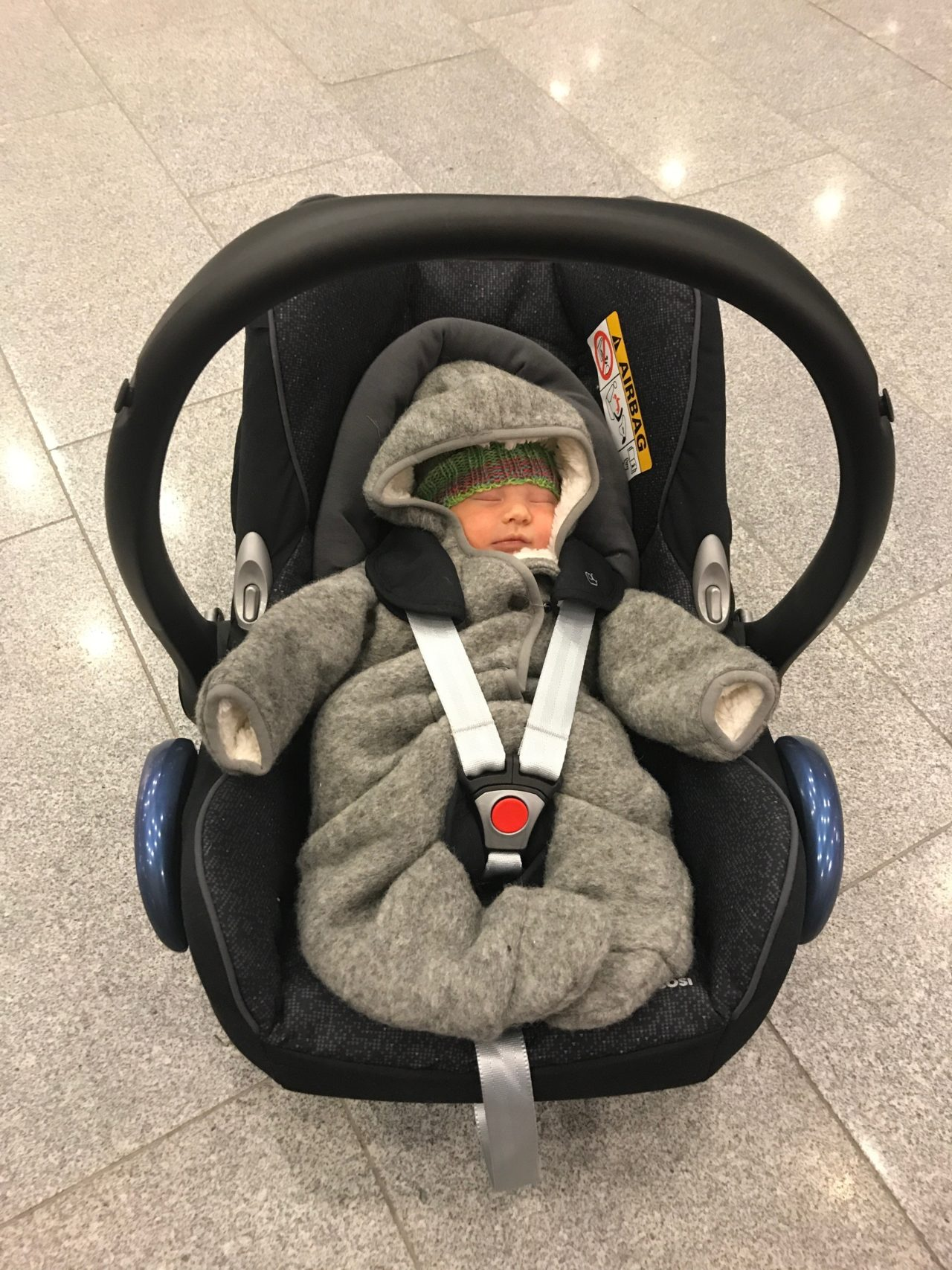 Newborn Boy In A Gray Winter Overall And Knitted Hat In Baby Car Seat