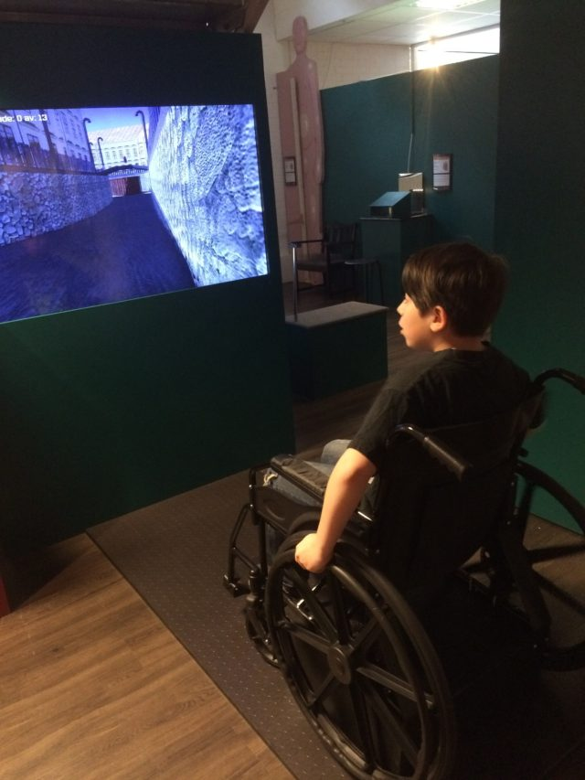 Boy With Brown Hair Sits In A Wheelchair And Plays Games On Big Screen