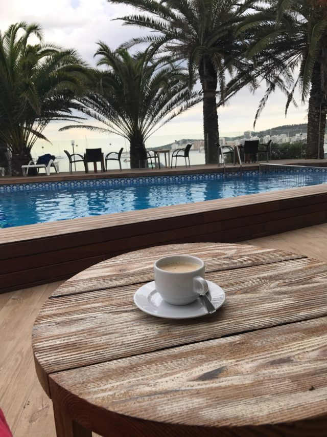 Coffee In A White Coffee Cup On A Wooden Table In A Hotel In Spain Overlooking Pool And Sea