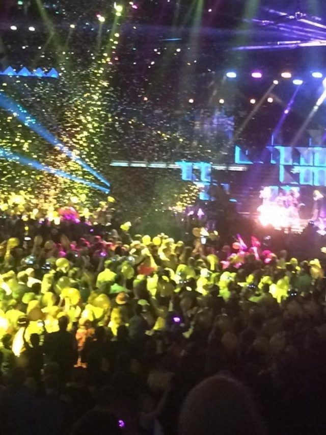 Concert With Headlights In Different Colors And Gold Confetti In Air