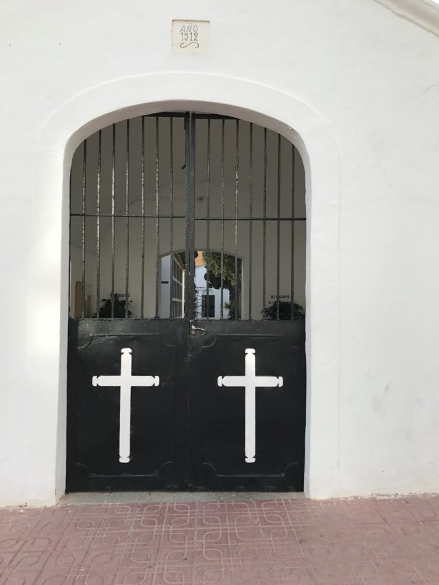 Black Steel Door With White Crosses And Grille At Cemetery With Red Stone Slabs On The Ground