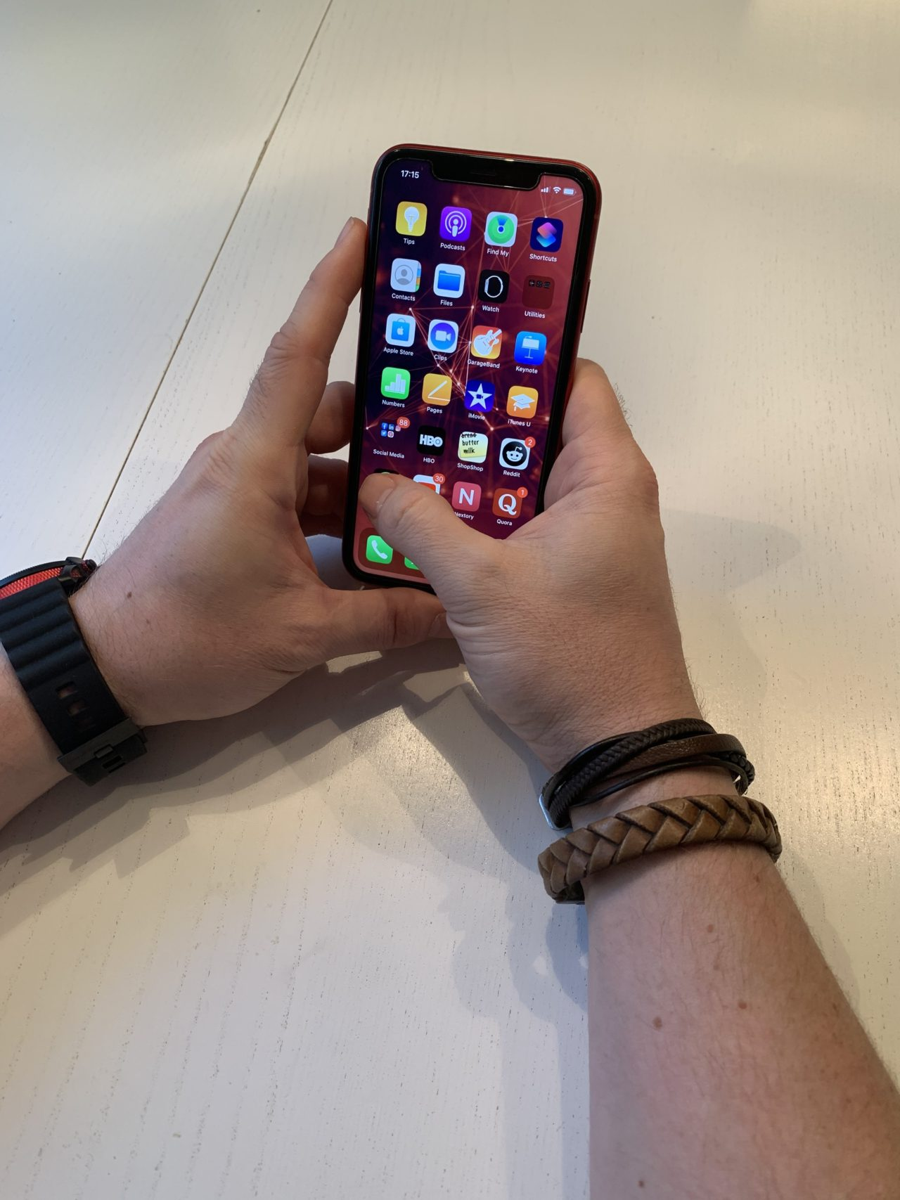 Man With Bracelets Holding A Red iphone With Apps Visible
