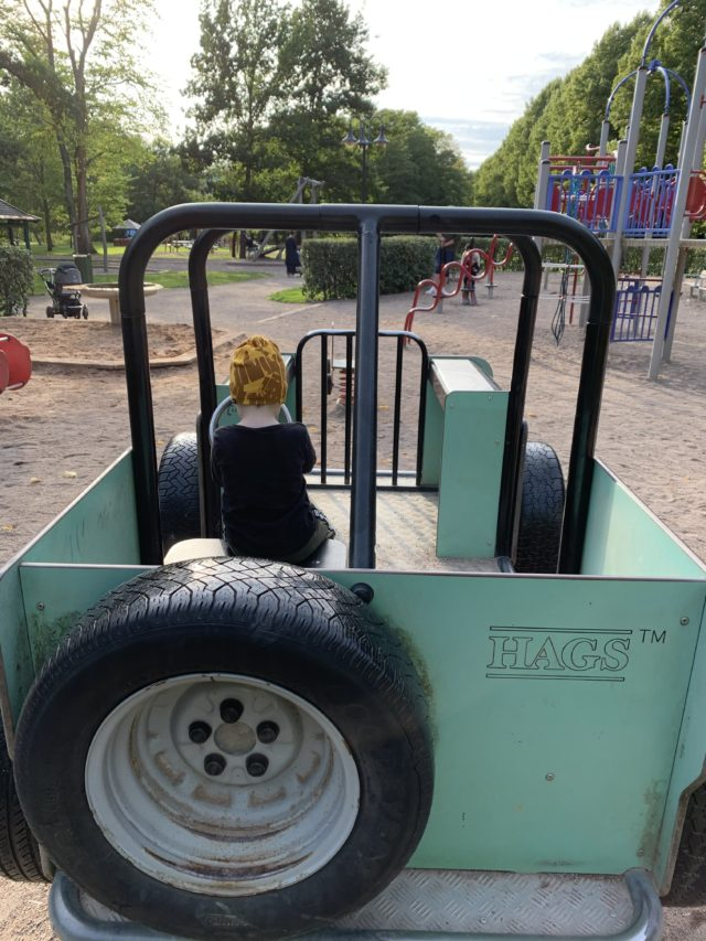 Kid Playing In A Jeep Car At A Playground