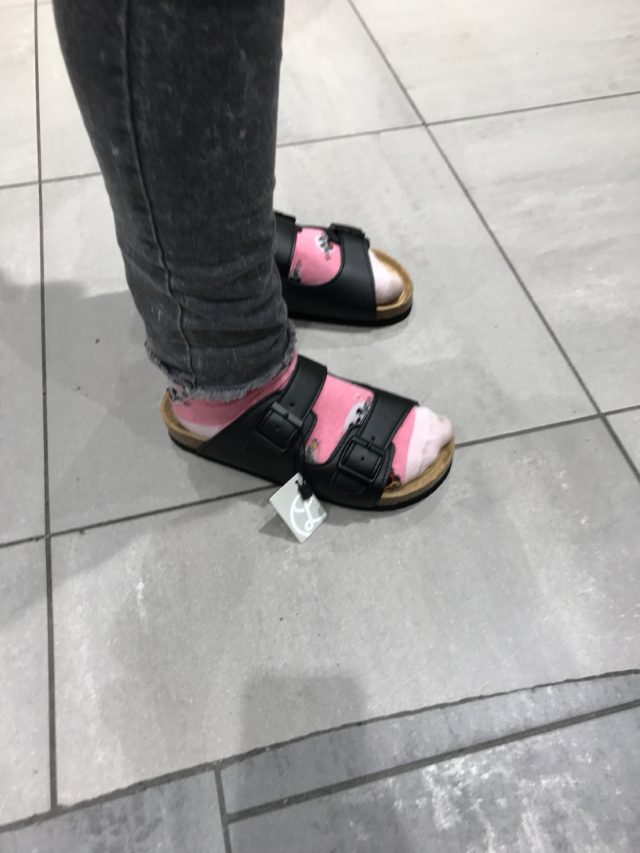 Slippers With Pink Socks And Black Jeans With A Light Gray Background