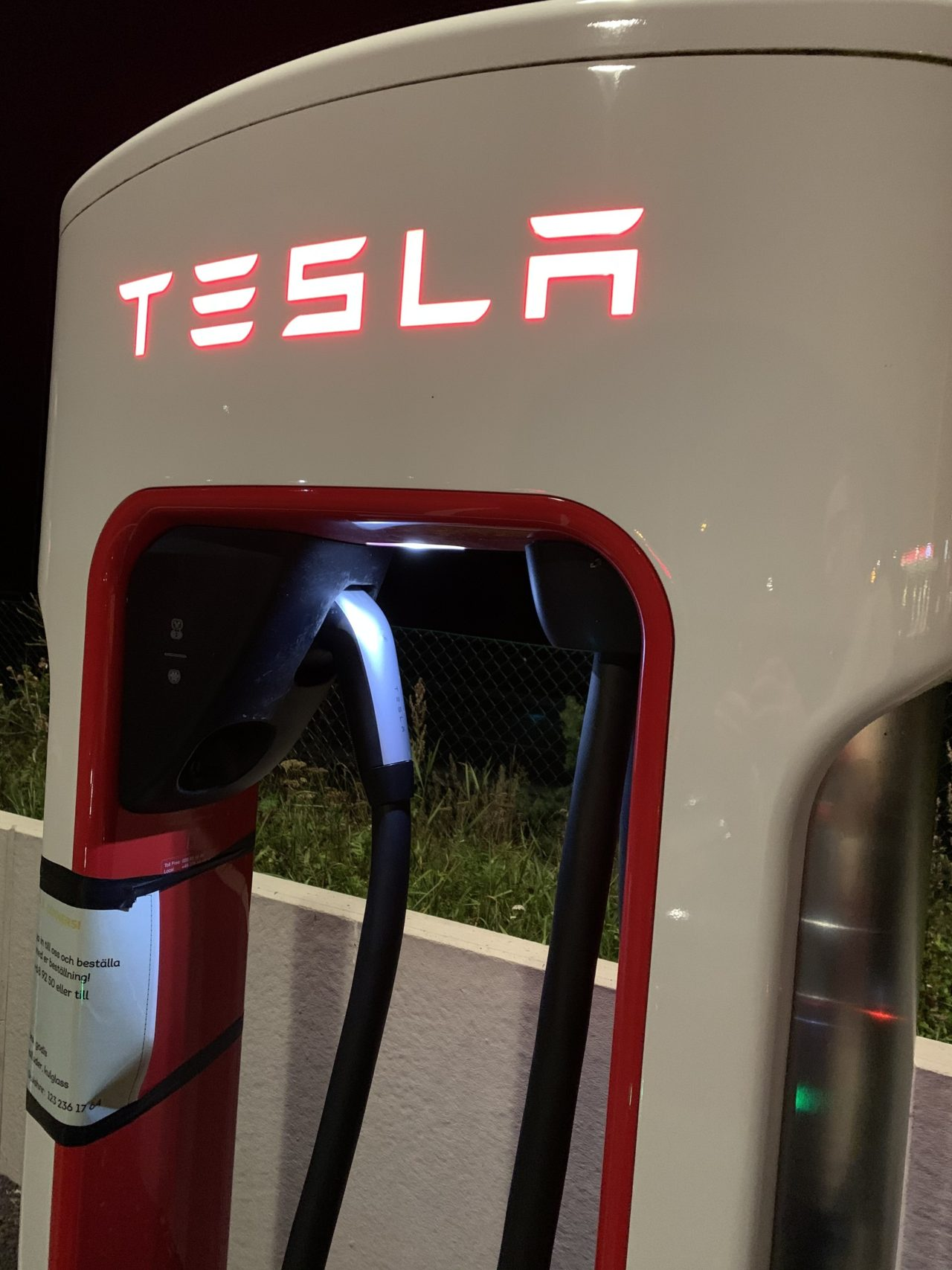 Tesla Supercharger Stall Station Glowing Sign And Charger Cord