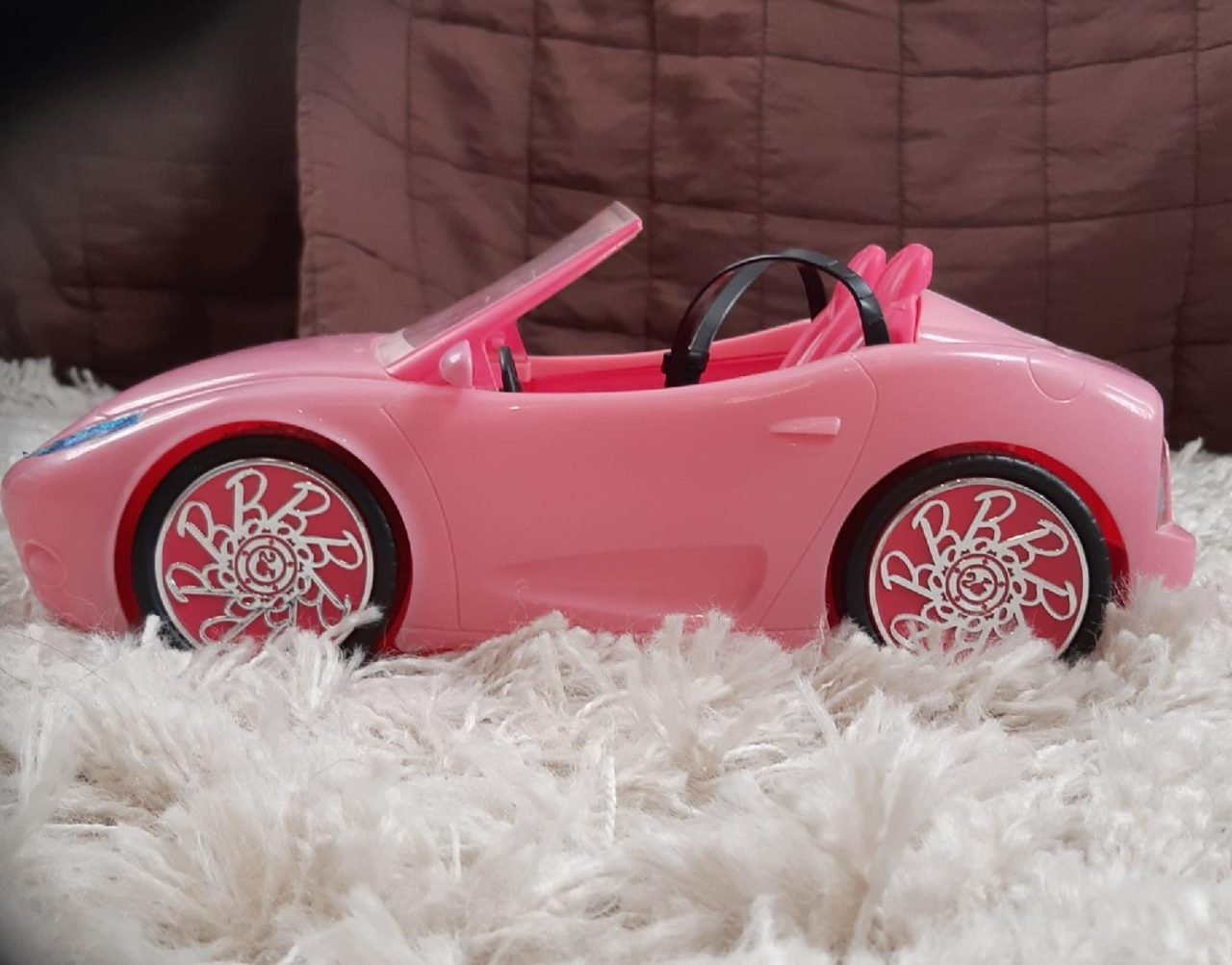 Pink Barbie Convertible Car From The Side On White Carpet With Brown Background