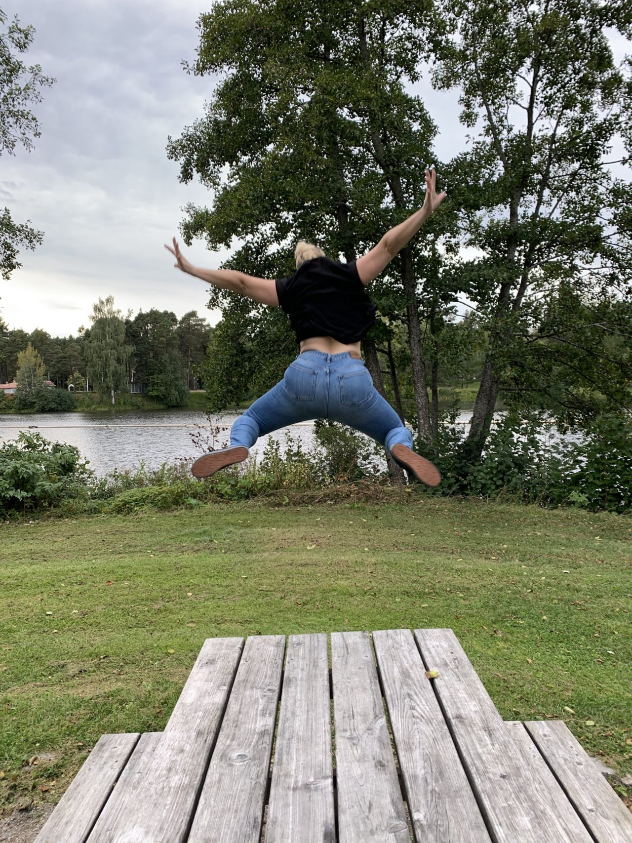 Woman In Black Shirt Jumping Off A Wooden Table