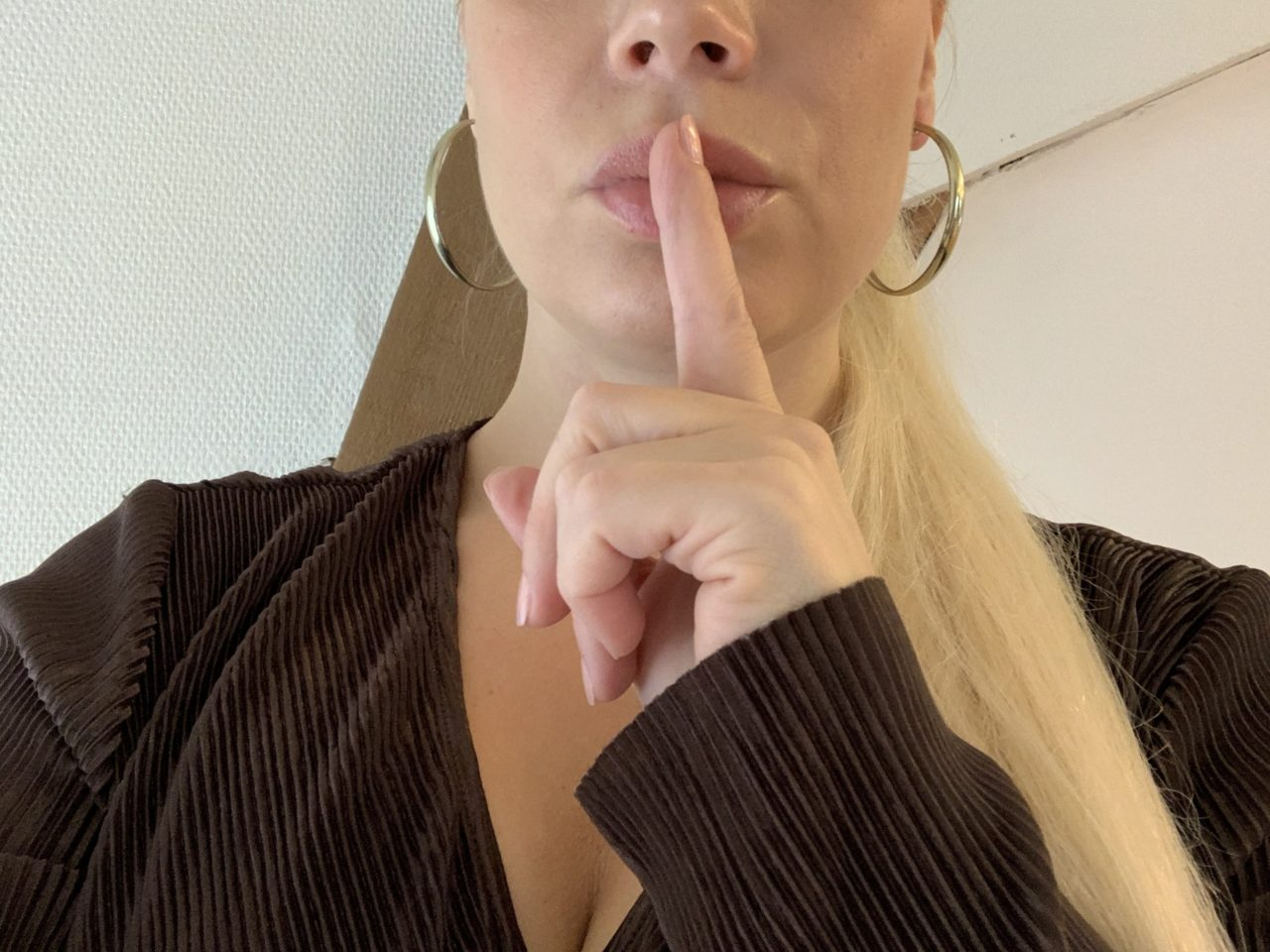 Woman holding Index Finger To Her Lips For Silence