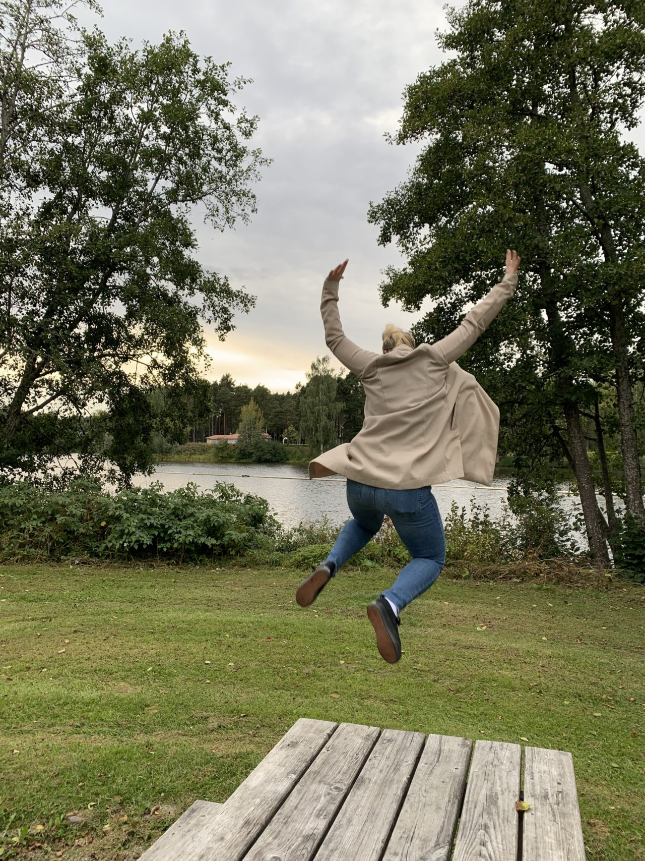 Woman In Beige Jacket Jumping Off A Wooden Table