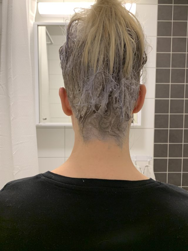 Woman Bleaching Outgrowth On Hair At Home In The Bathroom