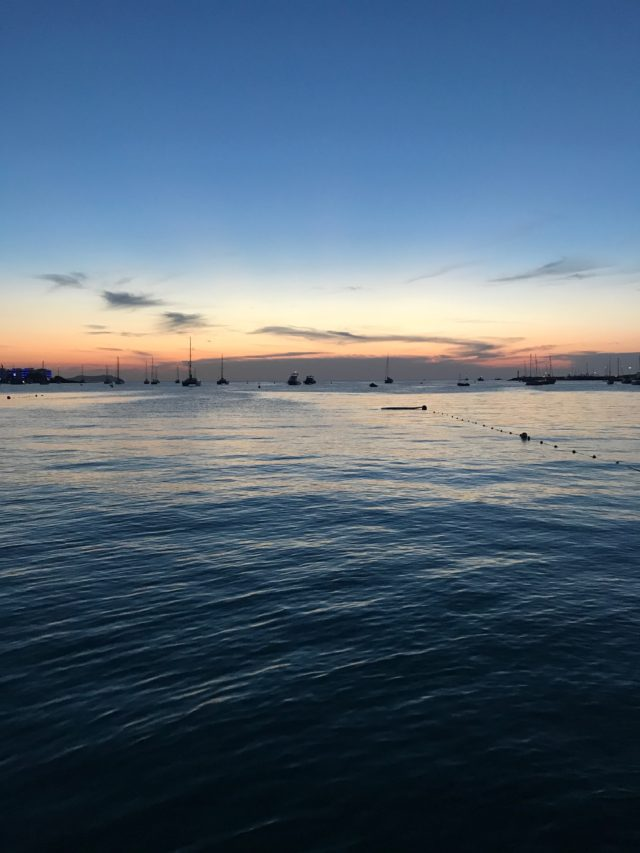 Blue Ocean Water At Sunset With Sail Boats In The Distance