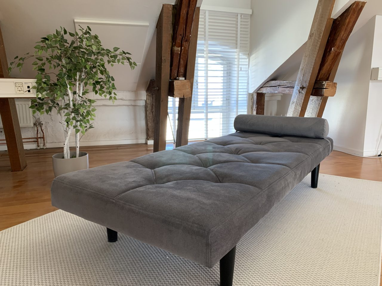 Grey Chaise On A White Carpet In A Penthouse Office