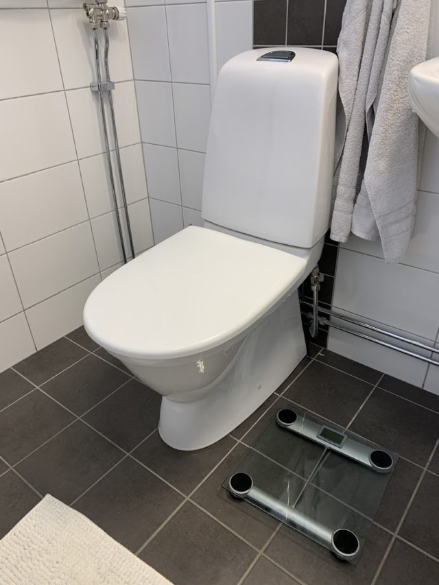 Clean Bathroom With A White Toilet And A Scale On The Floor