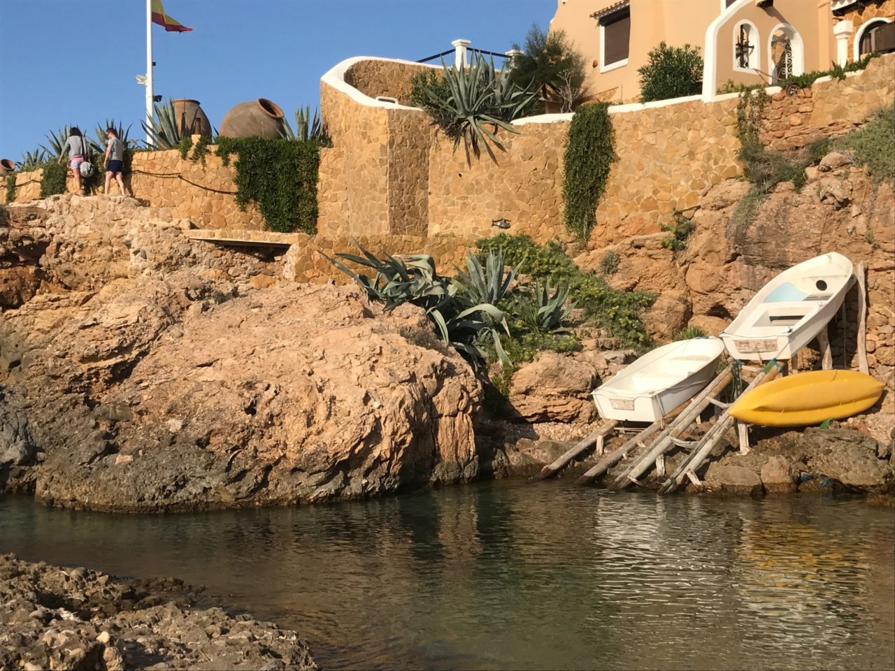 House On A Cliff With Boats And A Flag Pole