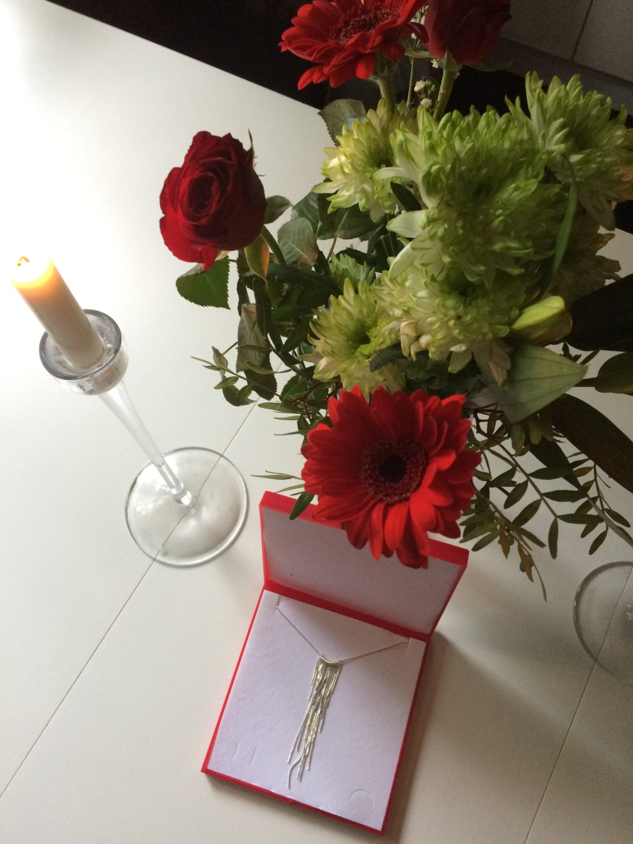Jewelry Gift With Flowers And A Lit Candle