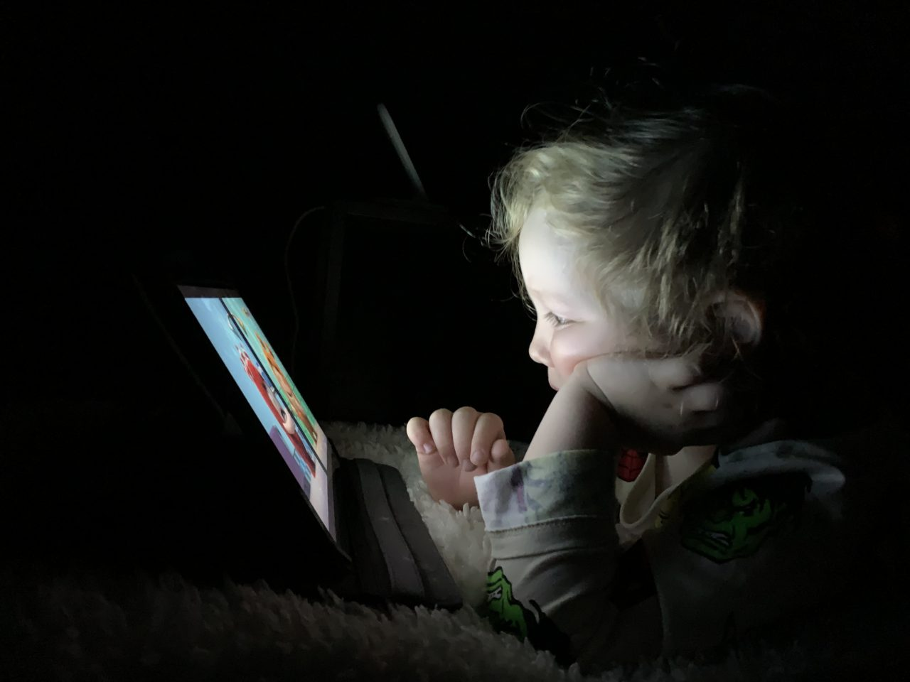 Kid Watching A Netflix Show On A Tablet In The Dark