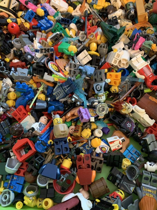 Lego Mini Figurines And Brick Pieces In A Green Collection Box