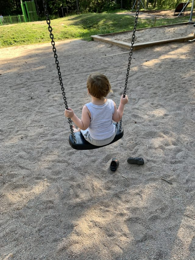 Small Kid Swinging On A Swing In Playground