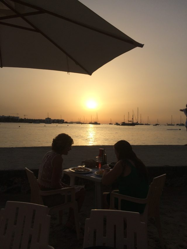 Sunset Dinner By The Sea With Boats And Umbrella