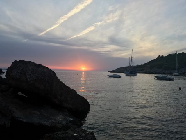 Rock By The Ocean In Front Of A Sunset With Boats
