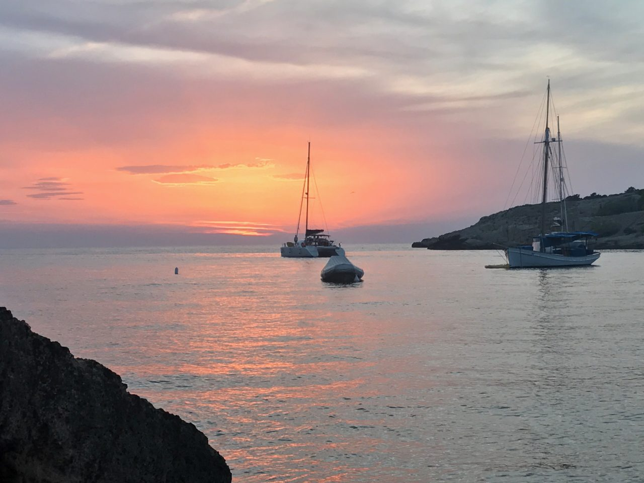 Sunset In Ibiza With Sail Boats In A Cove