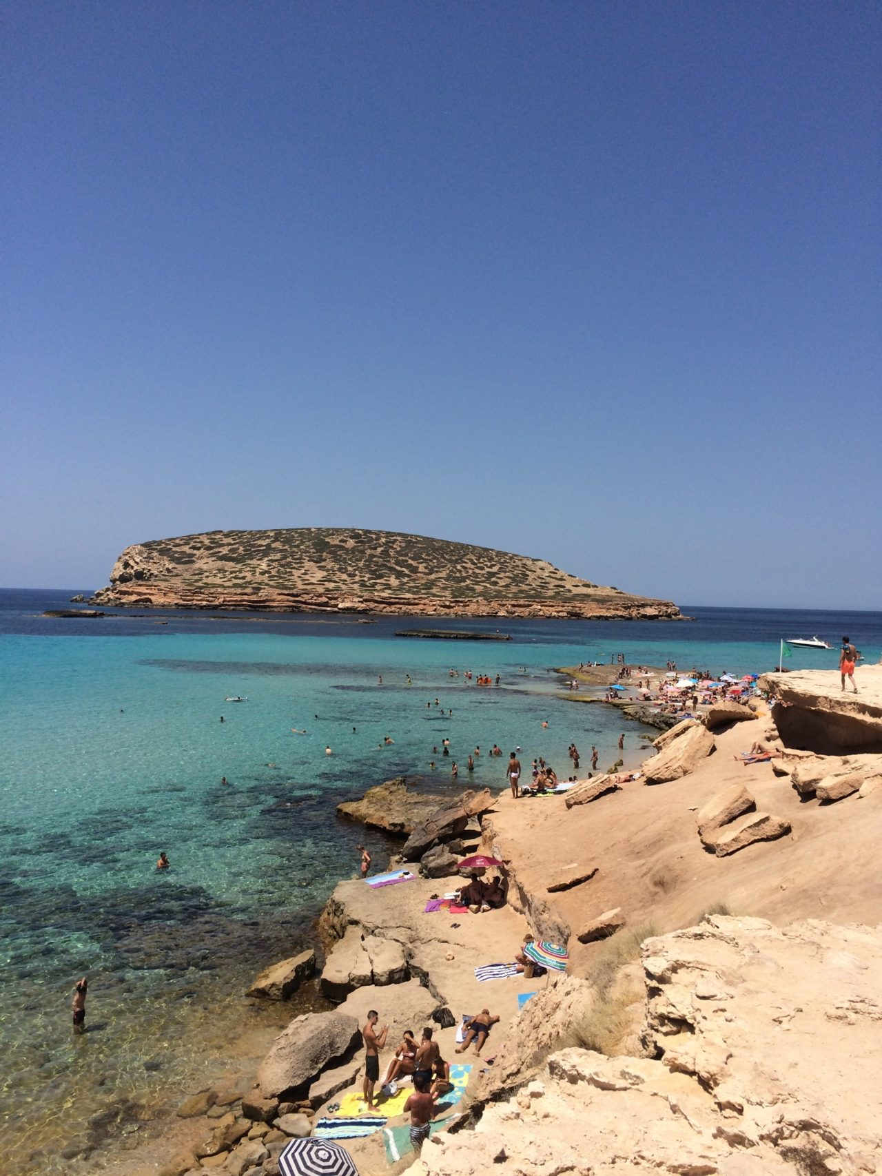 Beach With Sunbathers And Swimmers With An Island In Ibiza