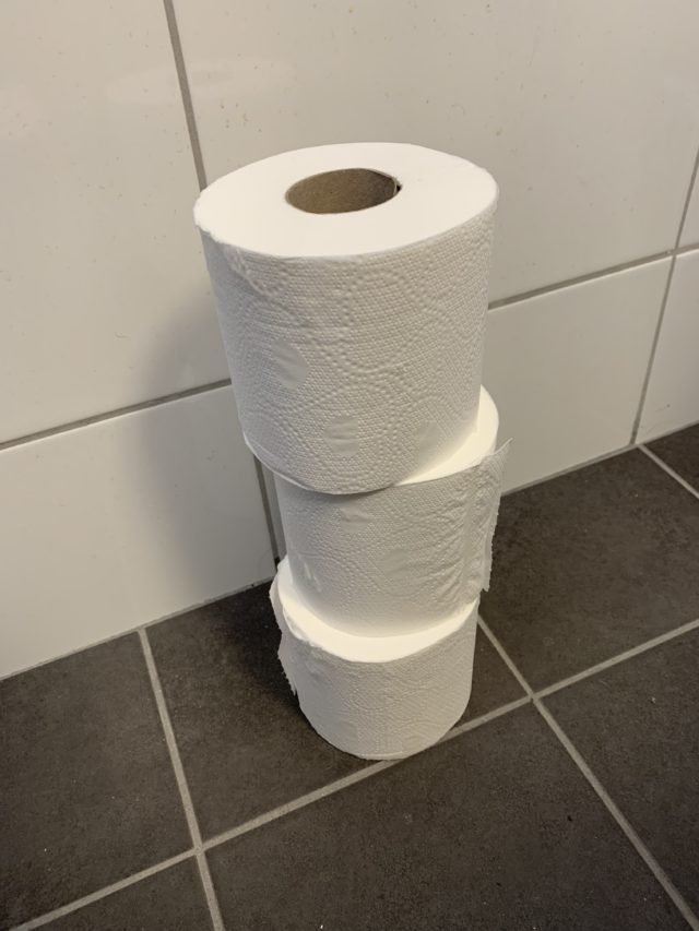 Stacked Toilet Paper Rolls On A Bathroom Floor