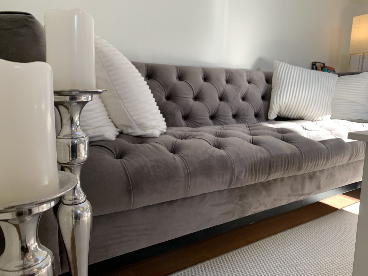 Velvet Couch With White Pillows And Candles