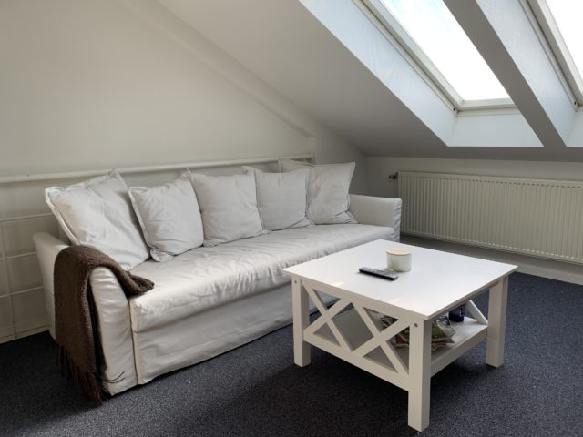 White Couch And Table In A Lounge With Skylight Windows