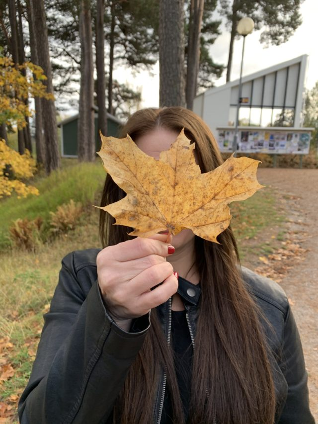 Woman Holding A Brown Leaf In The Fall